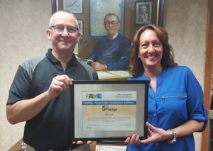 Dave Phillips, Talent Manager, and Dina Stuck, HR Director, hold GW Lisk's 5% Pledge Certificate.